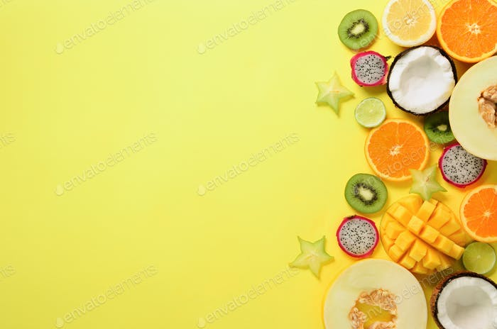 Exotic fruits on pastel yellow background - papaya, mango, pineapple, banana, carambola, dragon