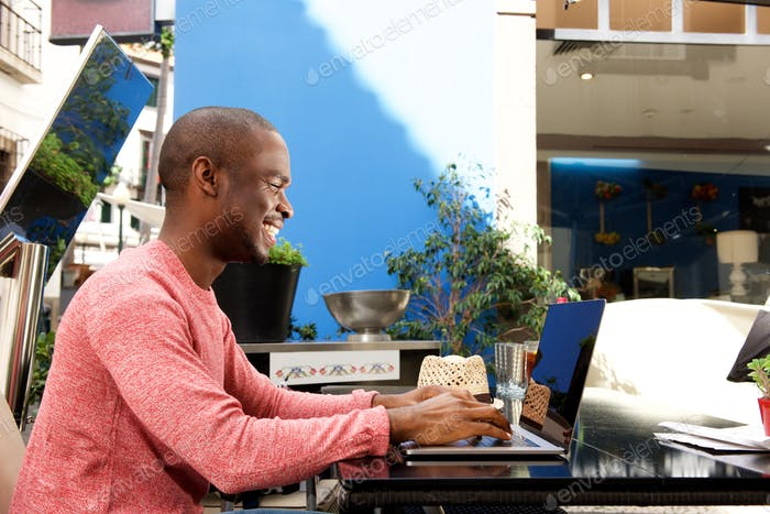 african american man sitting at cafe with laptop