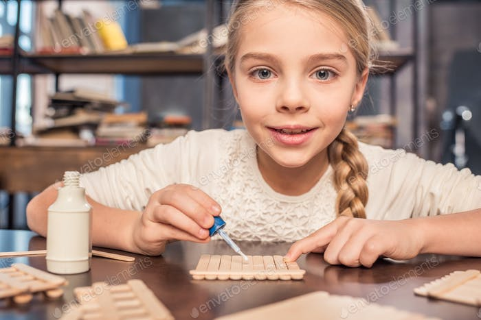 Smiling little girl handcrafting with ice cream sticks and glue