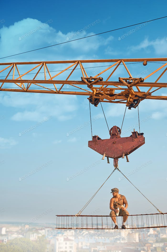 Crane holding iron construction, where sitting builder