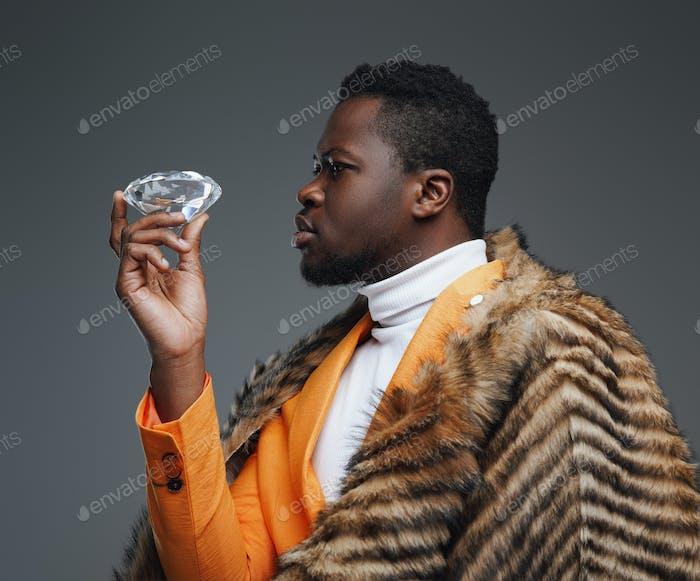 Reicher schwarzer Mann mit luxuriösem Diamanten und Fell