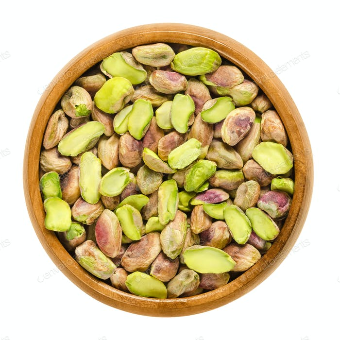 Shelled pistachio kernels in wooden bowl over white
