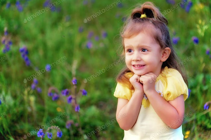 Cute funny baby girl scared of insect outdoors in green field. Child portrait