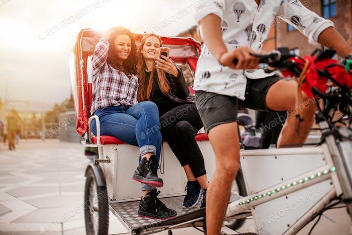 Junge Frauen sitzen auf Dreirad und schauen auf Handy