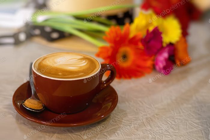 A cup of coffee with art on a table, blurred flowers on the background