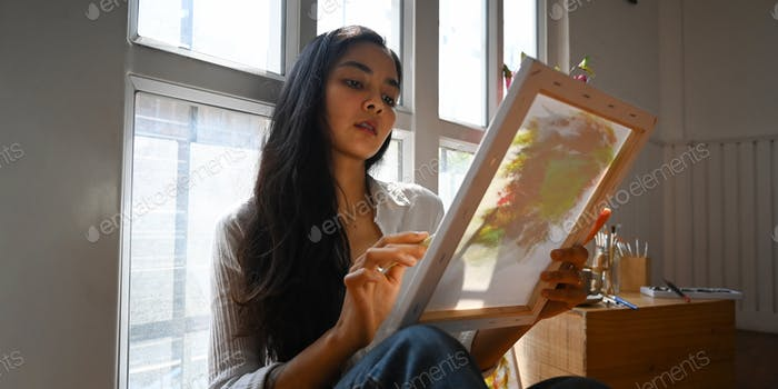 A beautiful woman painting on canvas with paintbrush.