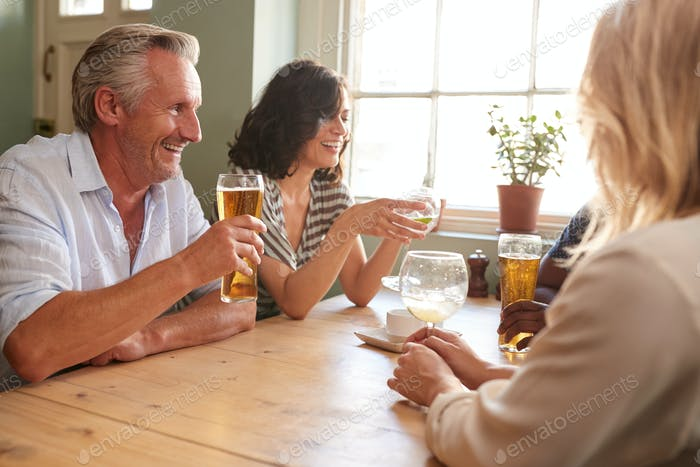 Mature adult friends drinking at a table in a pub