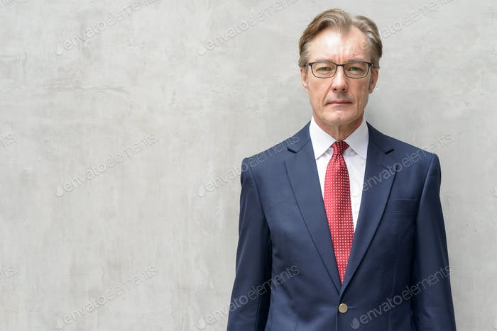 Handsome mature businessman in suit with eyeglasses against concrete wall