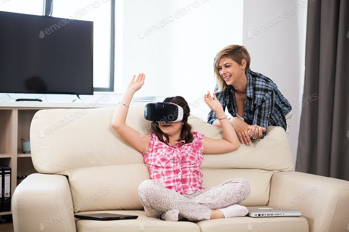 Happy kid wearing a virtual reality headset and plays games