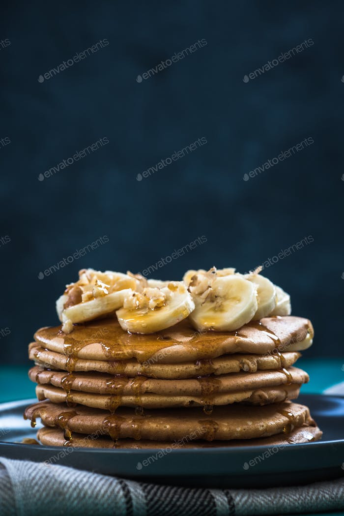 Pancakes pile with banana,walnuts and maple syrup.Copy space