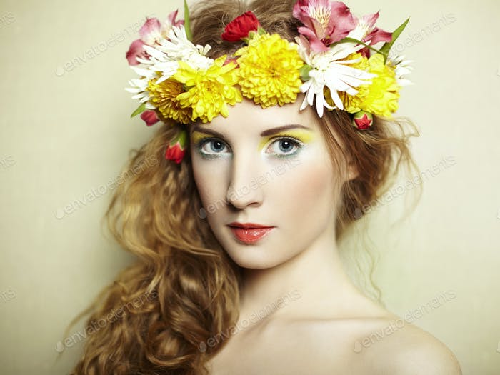 Schöne junge Frau mit zarten Blumen im Haar