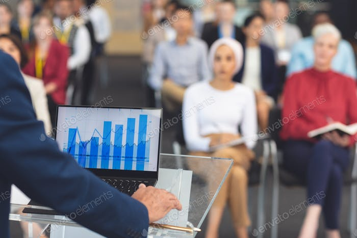 Businessman using graphs on his laptop while he speaks at a business seminar in modern office