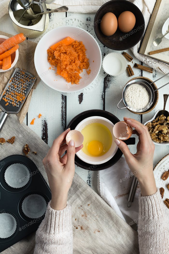 Woman Cracking Egg to Make Carrot Cupcakes