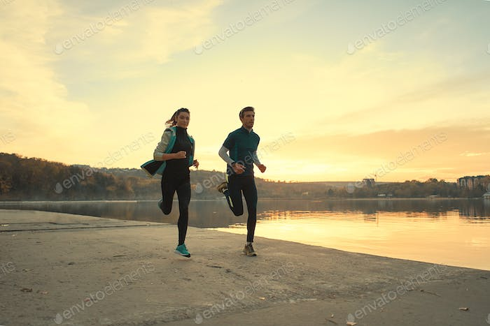 Young man and woman out for a run on the lake at the sunrise