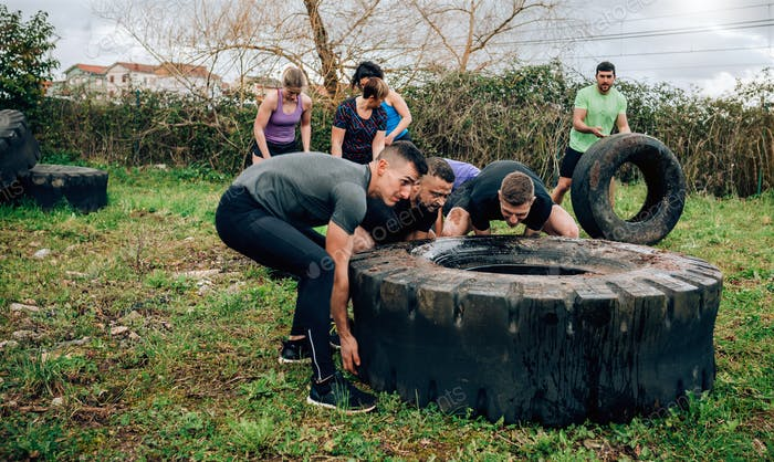Participants in an obstacle course turning a wheel