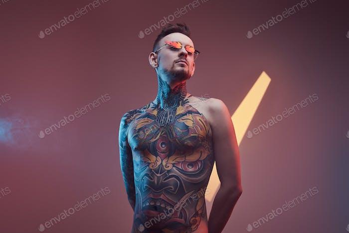 Tätowierte Hipster-Person mit nacktem Torso posiert auf buntem Hintergrund