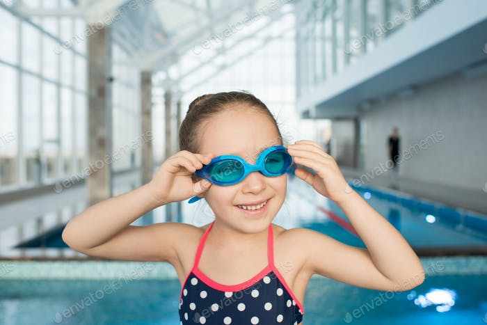 Happy little swimmer in modern pool