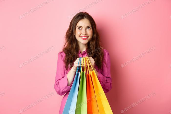 Cheerful young woman thinking of buying something, holding shopping bags with dreamy smile, buying