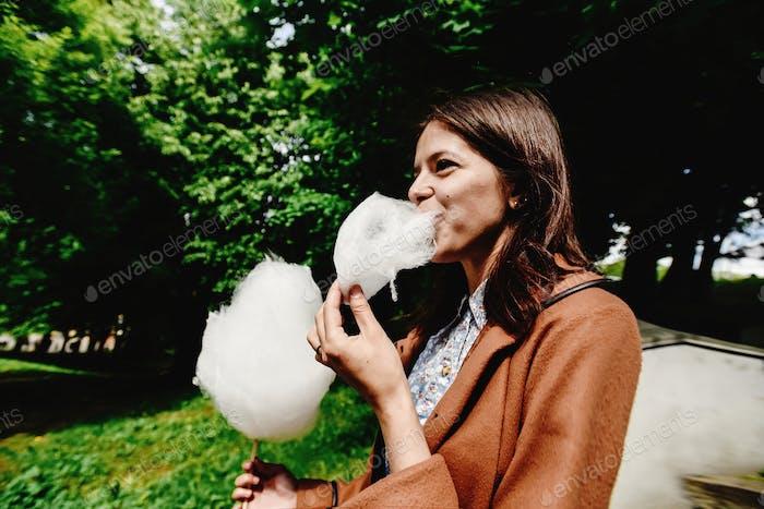 glückliches stilvolles Mädchen hält große Zuckerwatte und Essen im Vergnügungspark im sonnigen Frühling Zeit
