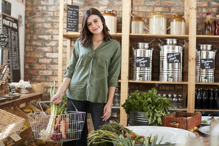 Portrait Of Woman Buying Fresh Fruit And Vegetables In Sustainable Plastic Free Grocery Store