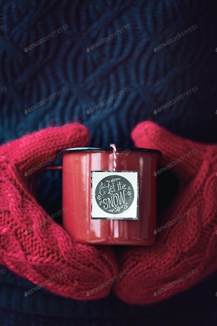 Mug of tea in woollen mittens