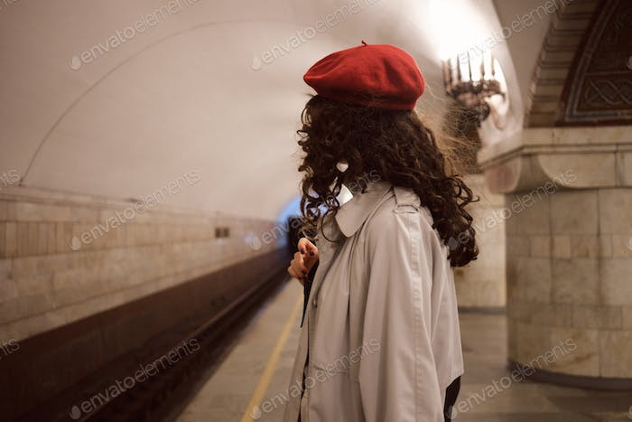 Side view of brunette girl in trench coat and red beret waiting train at metro station