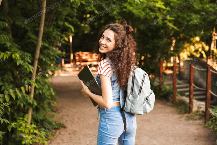 Photo of smiling caucasian woman 18-20 wearing backpack, walking