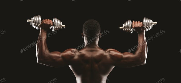 Back view of african fitness model pushing up the dumbbells