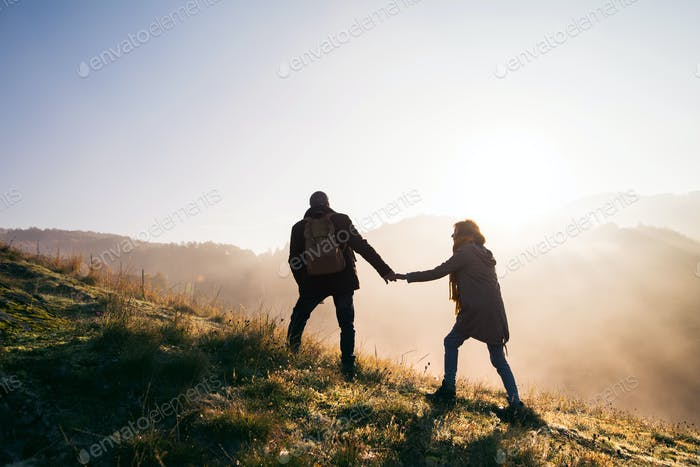 Senior couple on a walk in an autumn nature at sunrise.