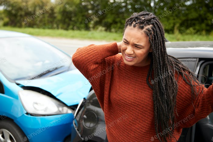 Female Motorist With Whiplash Injury In Car Crash Getting Out Of Vehicle