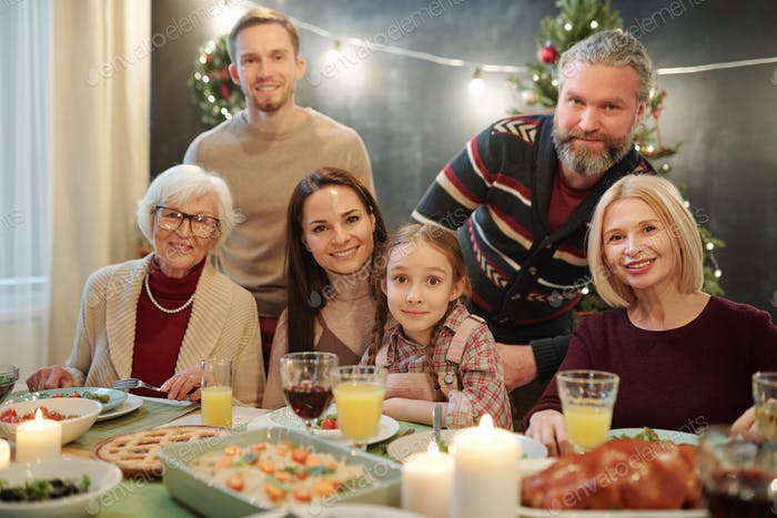 Big family looking at you while sitting by served table in front of camera