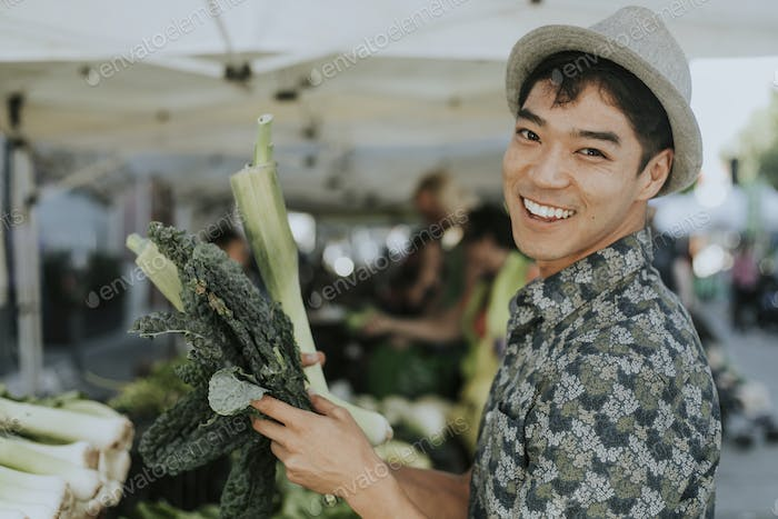 Man buying kale at a farmers market
