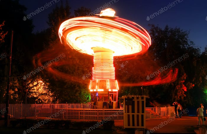 Blurred motion effect around of brightly illuminated rotating high speed carousel merry-go-round