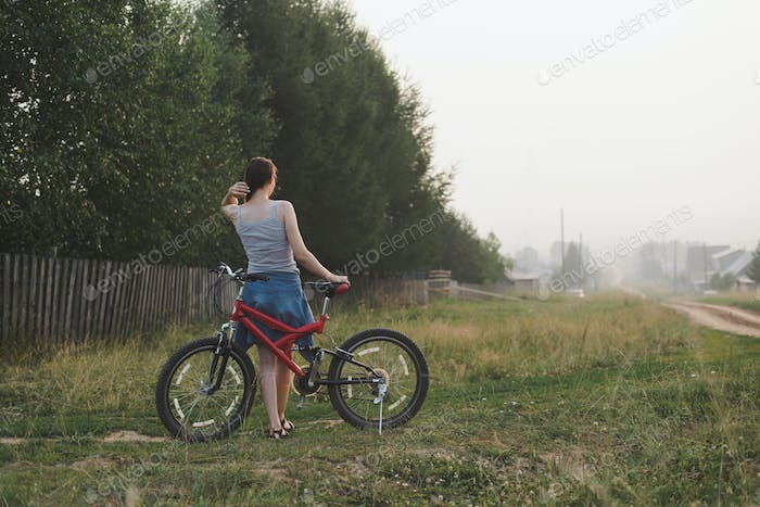 young woman standing with bicycle countryside near garden in village