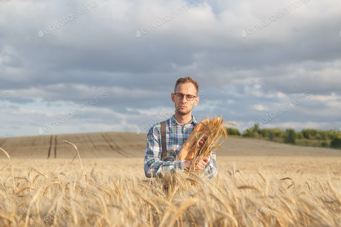 Farmer hold bakery products and ears of corn standing in ripe wheat field.