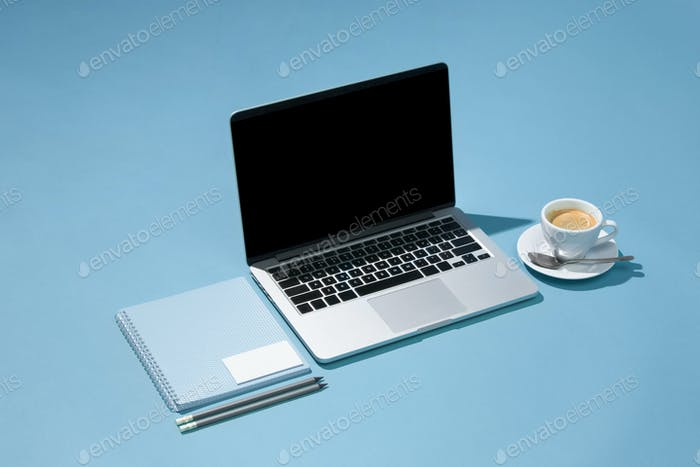 The laptop, pens, phone, note with blank screen on table