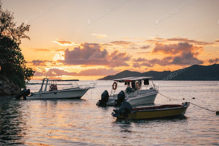 Fishing boats resting in sunset evening light near port of La Digue island, Seychelles. Praslin