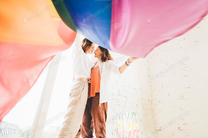 Lesbian couple in love standing near the window with the rainbow flag.