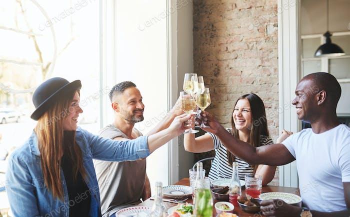 Gruppe junger Erwachsener, die zusammen am Tisch trinken