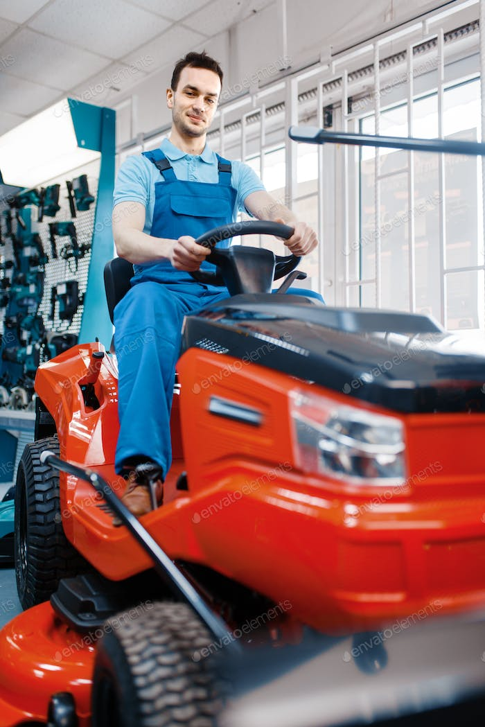 Male worker sitting on lawn mower in tool store