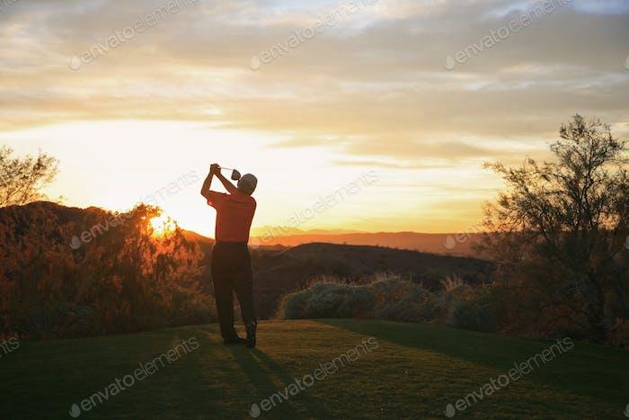 Golfista saliendo a la puesta de sol en el campo de golf.