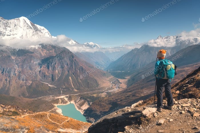 Standing woman against beautiful lake and mountains