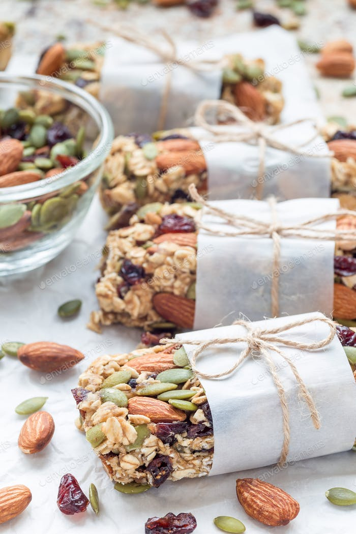 Homemade granola energy bars with figs, oatmeal, almond, dry cranberry and pumpkin seeds, vertical