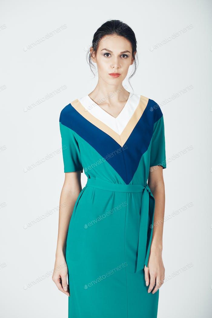 Modefoto der jungen prächtigen Frau in einem grünen Kleid