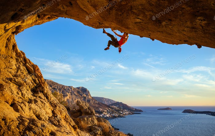 Male climber on overhanging rock against beautiful view of coast