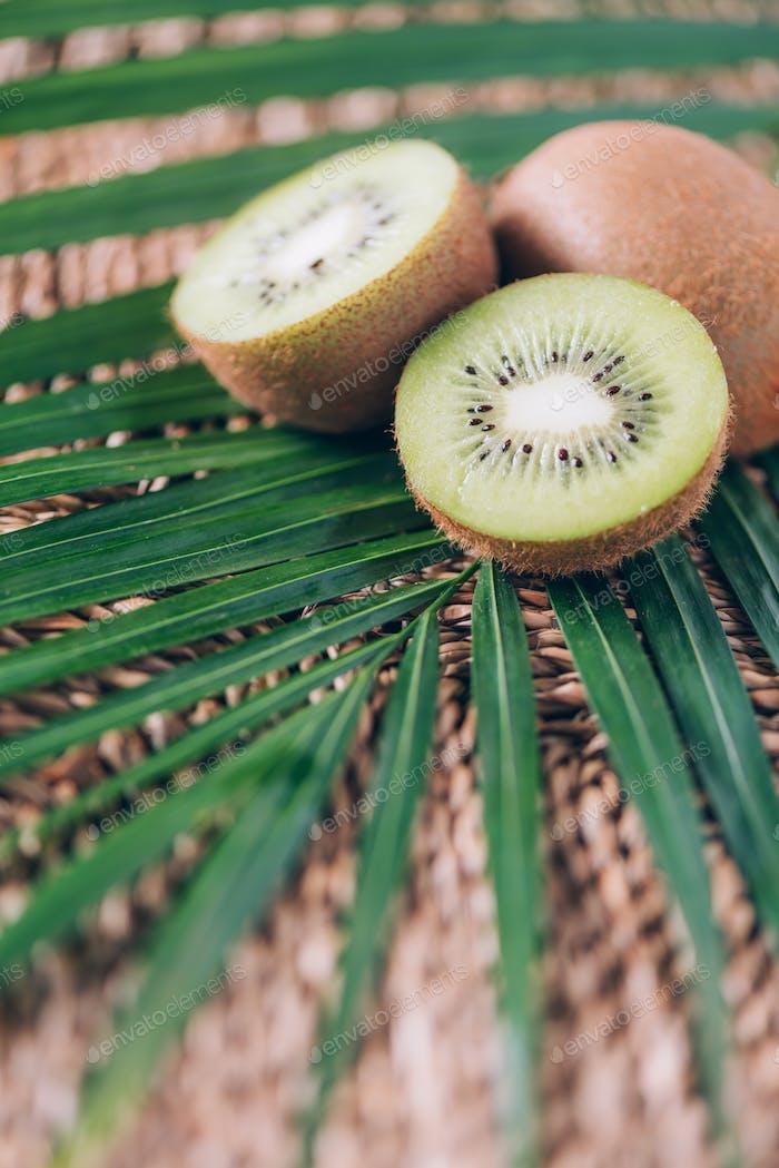 Saftige Kiwis über Palmblätter auf Rattan-Hintergrund. Kopierraum. Tropische Reise, exotische Früchte