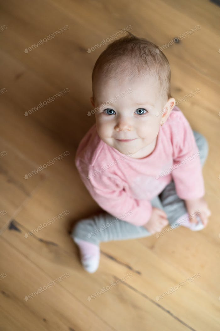 Cute little girl at home sitting on wooden floor, smiling
