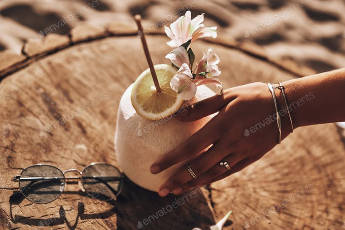 Aloha summer!  Close-up of young woman touching coconut cocktail with her hand