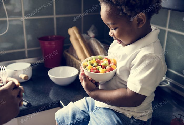 Black kid with fruit salad in the kitchen