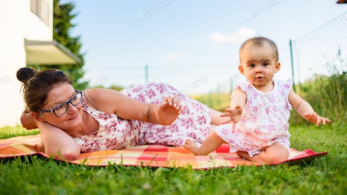 Adorable infant baby girl with mother on colorful blanket in green grass. Ninth months old child